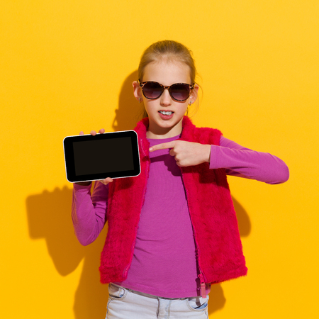 waist shot: Young blond girl pointing at a blank digital tablet screen. Waist up  studio shot on yellow background. Stock Photo