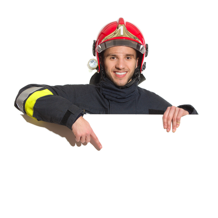 Smiling fireman in red helmet standing behind placard and pointing. Head and shoulders studio shot isolated on white. 스톡 콘텐츠