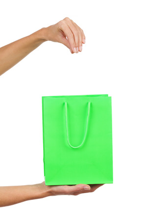 pull out: Close up of womans hand holding green shopping bag and pull out something. Studio shot isolated on white.