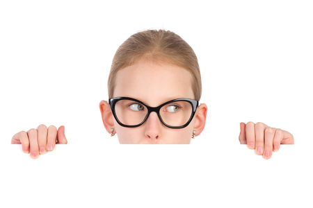 one child: Girl in black glasses peeking behind white placard and looking away. Studio portrait isolated on white.