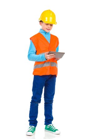 reflective vest: Young boy in yellow hard hat and orange reflective vest holding a digital tablet and reading. Three quarter length studio shot isolated on white.