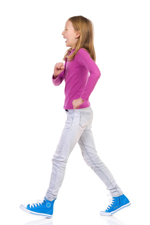 Walking teen girl, side view. Full length studio shot isolated on white.