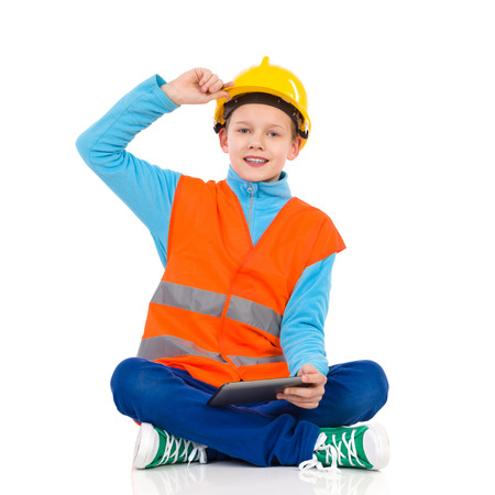 reflective vest: Young boy in yellow hard hat and orange reflective vest sitting on a floor with legs crossed, holding a digital tablet and looking at camera. Full length studio shot isolated on white. Stock Photo
