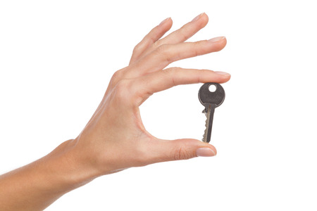 mujer sola: Cerca de la mano de la mujer la celebraci�n de una clave en los dedos. Tiro del estudio aislado en blanco. Foto de archivo
