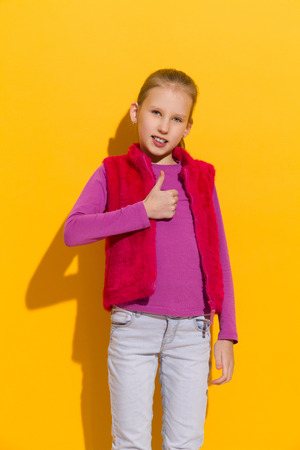 three quarter: Young blond girl posing with with thumb up. Three quarter length studio shot on yellow background.