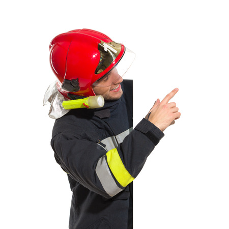 Smiling fireman in red helmet standing behind placard pointing and reading. Waist up studio shot isolated on white. 스톡 콘텐츠