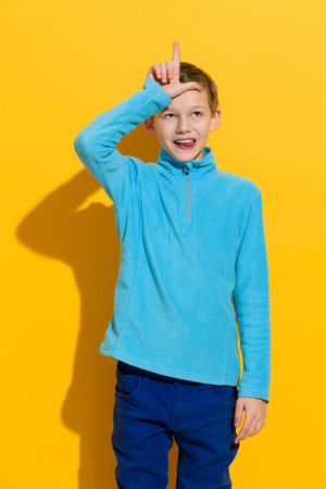 l hand: Young boy showing L hand sign for loser. Three quarter length length studio shot on yellow background. Stock Photo
