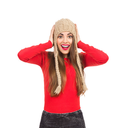 waist shot: Surprised girl in winter cup holding head in hands. Waist up studio shot isolated on white.
