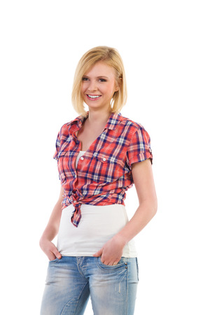 lumberjack shirt: Young woman in lumberjack shirt standing with hands in pockets. Three quarter length studio shot isolated on white. Stock Photo