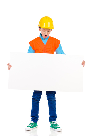 preadolescence: Surprised young boy in yellow hard hat and orange reflective vest standing and holding placard. Full length studio shot isolated on white.