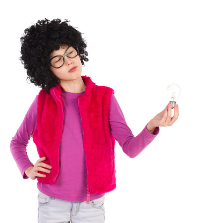 waist shot: Thinking girl in curly wig and black glasses holding and looking at a light bulb. Waist up length studio shot isolated on white. Stock Photo