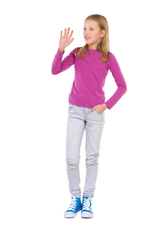 Young girl waving hand and looking away. Full length studio shot isolated on white.