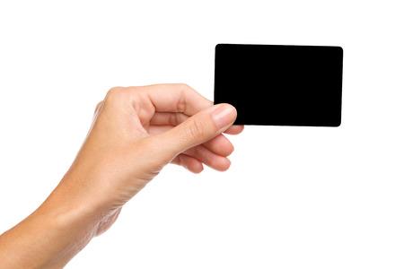 空白のブラック カードを持っている女性の手のクローズ アップ。スタジオ撮影で孤立したホワイトです。