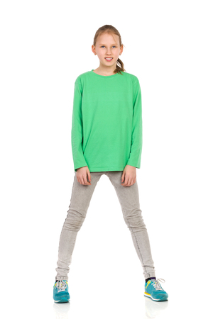 legs apart: Ten Years old blond girl in green blouse, jeans and sneakers standing legs apart and looking at camera. Full length studio shot isolated on white.