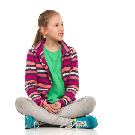 fleece: Cheerful blond girl in striped fleece blouse, jeans and sneakers sitting on floor with legs crossed and looking away. Full length studio shot isolated on white. Stock Photo