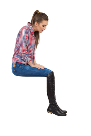 lumberjack shirt: Young woman in lumberjack shirt, jeans and black boots sitting on a top and looking down. Side view. Full length studio shot isolated on white. Stock Photo