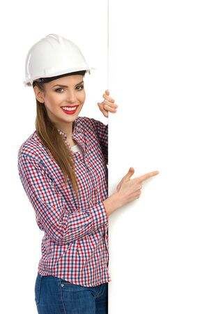 lumberjack shirt: Smiling beautiful young woman in white hardhat and lumberjack shirt holding big white banner and pointing. Waist up studio shot isolated on white.