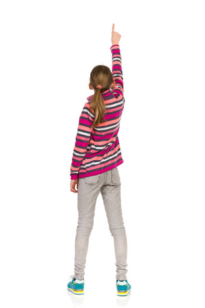 fleece: Little girl in striped fleece jacket, jeans and sneakers standing with arm raised and pointing. Rear view. Full length studio shot isolated on white.