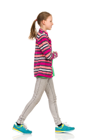 Smiling teen girl in striped fleece jacket, jeans and sneakers walking and looking away. Side view. Full length studio shot isolated on white.