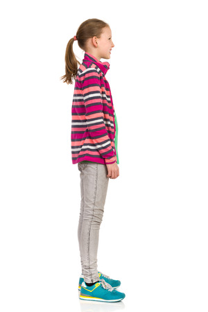 Smiling teen girl in striped fleece jacket, jeans and sneakers standing and looking away. Side view. Full length studio shot isolated on white. Standard-Bild