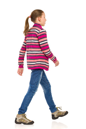 Teen girl in striped fleece jacket, jeans and hiking boots walking and looking away. Side view. Full length studio shot isolated on white.