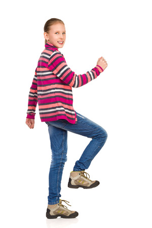 fleece: Smiling little girl in striped fleece jacket, jeans and hiking boots walking upstairs and looking at camera. Side view. Full length studio shot isolated on white.