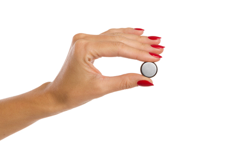 lithium: Close up of womans hand with red nails holdinga small shiny lithium battery. Studio shot isolated on white.