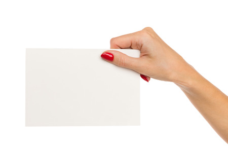 Close up of woman's hand with red nails holding blank white paper sheet. Studio shot isolated on white.