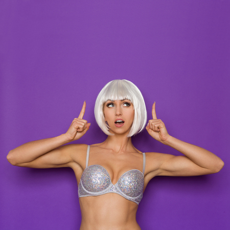 platinum hair: Cheerful young woman in a platinum wig and silver bra pointing and looking up at copy space. Waist up studio shot on purple background.