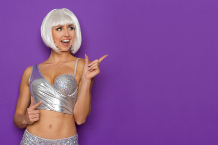 platinum hair: Shouting young woman in a platinum wig and silver bra pointing and looking away. Waist up studio shot on purple background.