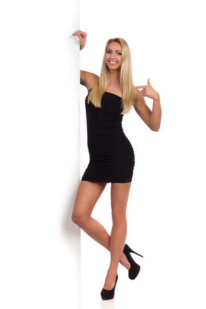 Sexy blond woman in black mini skirt and high heels standing close to big white banner and pointing. Full length studio shot isolated on white.