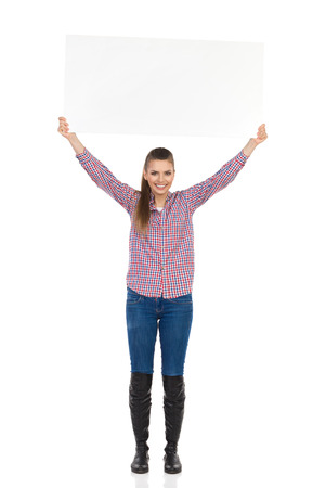lumberjack shirt: Smiling young woman in jeans, black boots and lumberjack shirt standing and holding white placard over her head. Full length studio shot isolated on white. Stock Photo