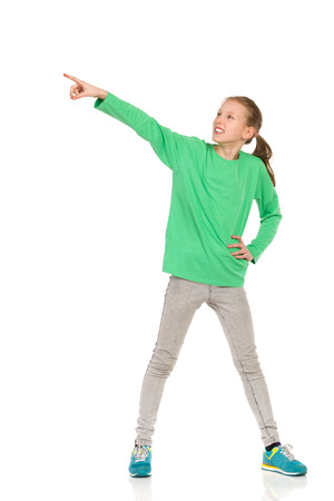 legs apart: Smiling girl in green blouse, jeans and sneakers standing legs apart, pointing and looking away. Full length studio shot isolated on white. Stock Photo