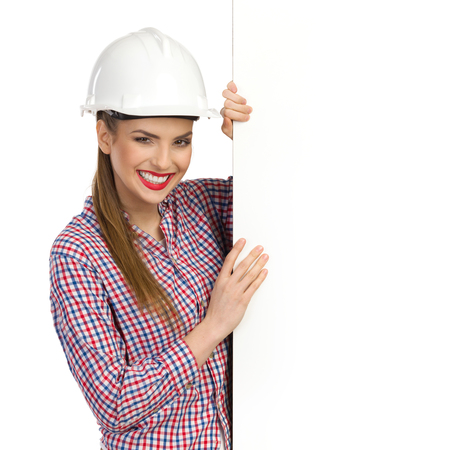 lumberjack shirt: Smiling beautiful young woman in white hardhat and lumberjack shirt standing and holding big white banner. Waist up studio shot isolated on white.