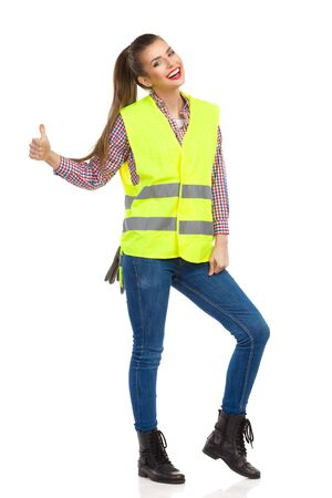 reflective vest: Smiling young woman in lime green reflective vest showing thumb up and looking at camera. Full length studio shot isolated on white.