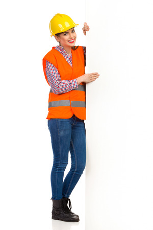 lumberjack shirt: Smiling young woman in yellow hardhat, orange reflective vest and lumberjack shirt standing close to a big banner and holding it. Full length studio shot isolated on white. Stock Photo