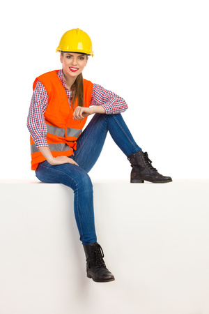 lumberjack shirt: Cheerful young woman in yellow hardhat, orange reflective vest, lumberjack shirt, jeans, black boots, sitting relaxed on top and looking at camera. Full length studio shot isolated on white.