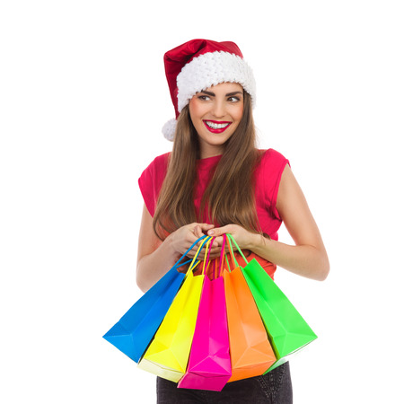 waist shot: Cheerful christmas girl holding colorful shopping bags and looking away. Waist up studio shot isolated on white.