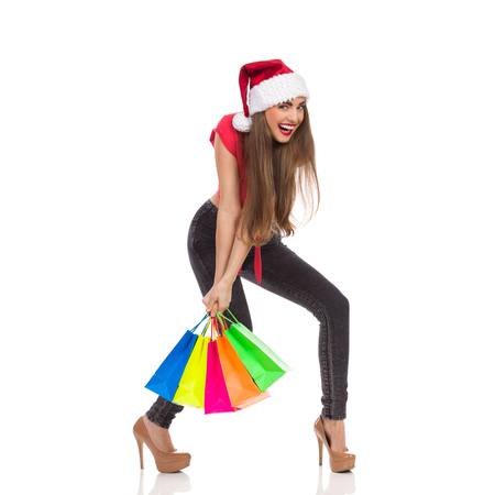 carrying heavy: Smiling christmas girl carrying heavy colorful shopping bags. Full length studio shot isolated on white. Stock Photo