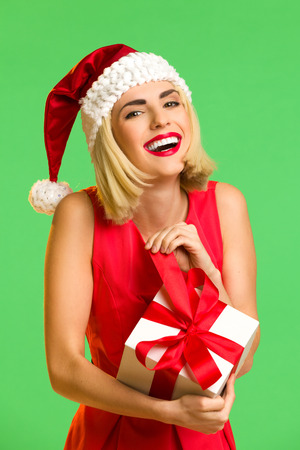 waist shot: Smiling young woman in santas hat opening a gift. Waist up studio shot isolated on green. Stock Photo