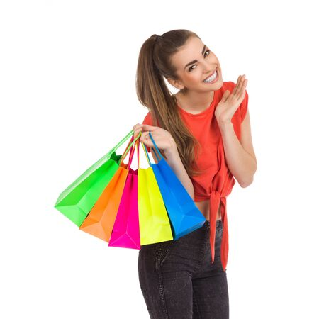 waist shot: Smiling girl posing with multicolored shopping bags. Waist up studio shot isolated on white.