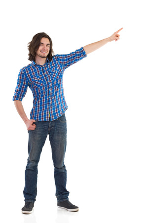 lumberjack shirt: Handsome young man standing with arm raised, pointing and looking at camera. Full length studio shot isolated on white. Stock Photo
