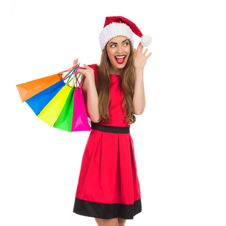 three quarter: Christmas girl with colorful shopping bags shouting and waving hand. Three quarter length studio shot isolated on white.