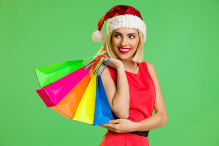 waist shot: Smiling young woman in santas hat posing with a colorful shopping bags. Waist up studio shot isolated on green.