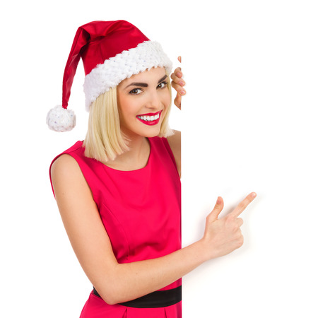 waist shot: Smiling blonde christmas girl behind a placard peeking and pointing. Waist up studio shot isolated on white.
