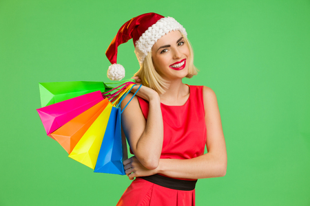 waist shot: Beautiful young woman in santas hat posing with a colorful shopping bags. Waist up studio shot isolated on green.