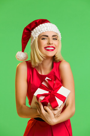 waist shot: Happy young woman in santas hat cuddle a gift. Waist up studio shot isolated on green.