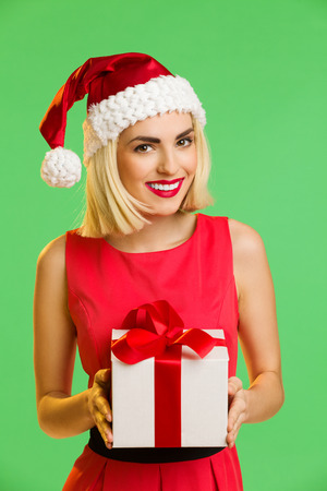 waist shot: Beautiful young woman in santas hat holding a gift. Waist up studio shot isolated on green. Stock Photo
