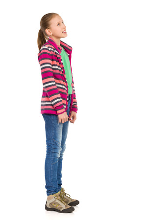 Smiling girl in striped fleece blouse, jeans and hiking boots standing and looking away. Side view. Full length studio shot isolated on white.