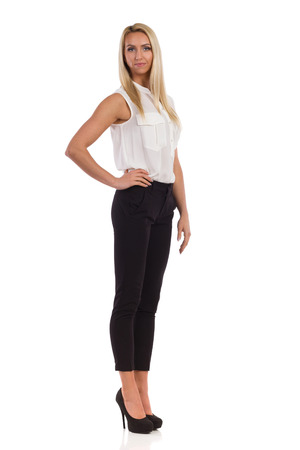 platinum hair: Young blond woman in white shirt, black pants, and high heels standing with hand on hip and looking at camera. Full length studio shot isolated on white.